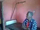 Un habitant du village sur un lit de patient abandonné, bouleversé par la bonne nouvelle de la mission prochaine.